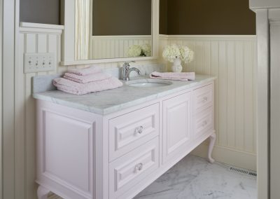 Feminine bathroom with pink vanity and white wainscotting