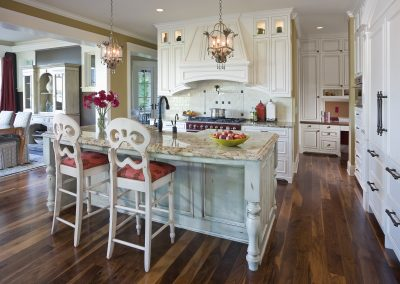 French country kitchen with white cabinets, colorful accents and red stove