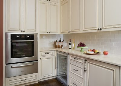 Kitchen pantry with built in oven and warming tray and wine refrigerator.