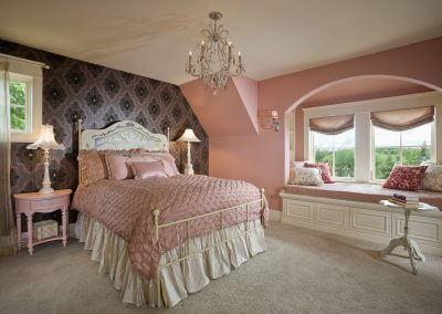 Pink girl's bedroom with velvet flocked designer wallpaper and window seat